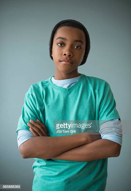 Stylish Black boy standing with arms crossed