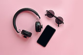 stylish black sunglasses,smartphone and headphones on pink background, flat lay. modern hipster image. black items on pink paper. instagram blogging. space for text. summer vacation