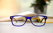 Stylish blue glasses on a blur background.