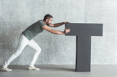 Need more time concept. Full length of concentrated young pleasant man is pushing big letter t. He is demonstrating persistence and endurance. Gray wall in background