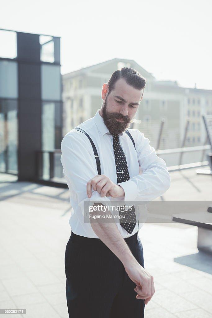 Stylish businessman rolling up sleeves on footbridge