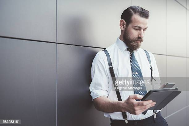 Stylish businessman using digital tablet and smartphone outside office