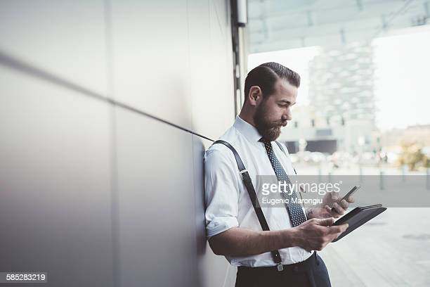 Stylish businessman using smartphone and digital tablet outside office
