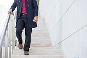 Stylish young Caucasian businessman wearing coat going downstairs outdoors. Business and fashion concept
