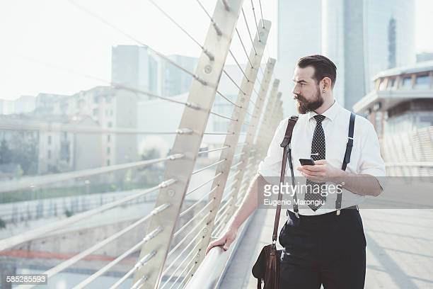 Stylish businessman with smartphone looking out from city footbridge