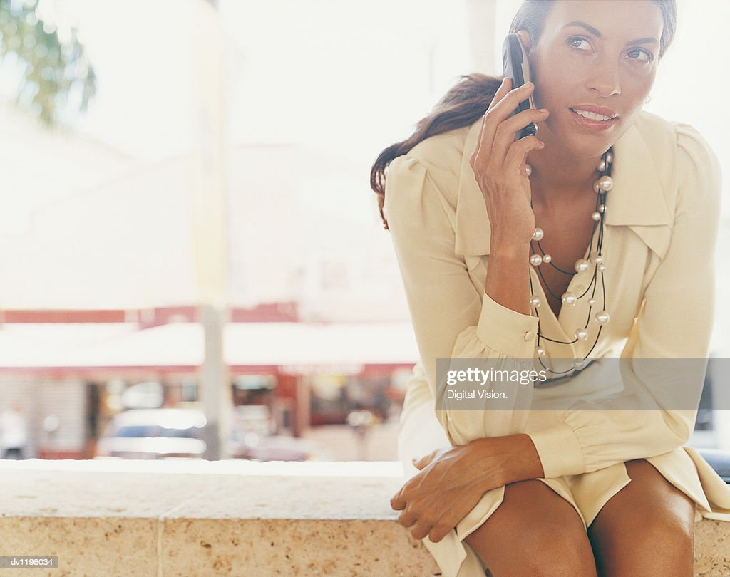 Stylish Businesswoman Sitting on a Wall Using a Mobile Phone : Stock Photo