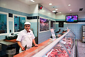 Stylish butcher with meat cleaver at SA Supermarket.