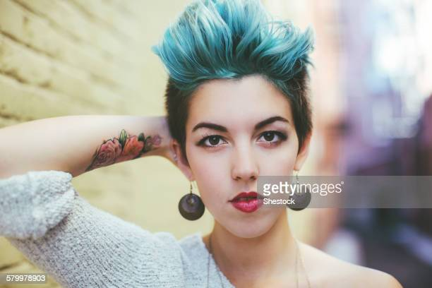 Stylish Caucasian woman with earrings and dyed hair