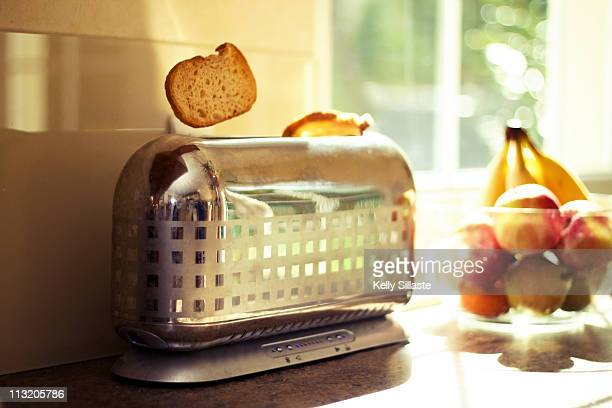 Stylish chrome toaster popping up toast