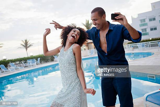 Stylish couple taking dance smartphone selfie at hotel poolside, Rio De Janeiro, Brazil