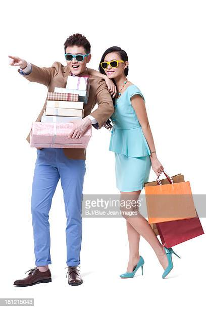 Stylish couple with shopping bags looking at view