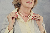 Stylish Elderly woman getting ready to go out. Active senior lifestyle. Close up of old female manicured hands , jewellery, fashion details. Vintage image