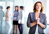 Image of pretty business leader looking at camera with interacting partners at background