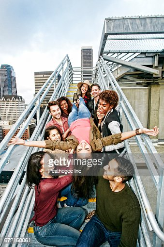 Stylish friends holding woman upside-down on urban metal staircase