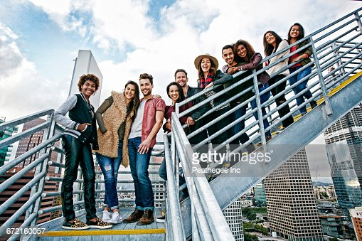 Stylish friends posing on urban metal staircase