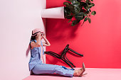 side view of beautiful stylish girl in hat and sunglasses sitting in upside down studio