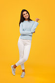 Young casual woman in sweater standing confidently on yellow backdrop pointing away.