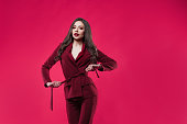 Stylish glamorous girl tightens the belt. concept of diet and weight loss. Attractive young brunette dressed in fuchsia color, fuchsia color background
