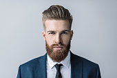 Stylish handsome bearded businessman looking at camera
