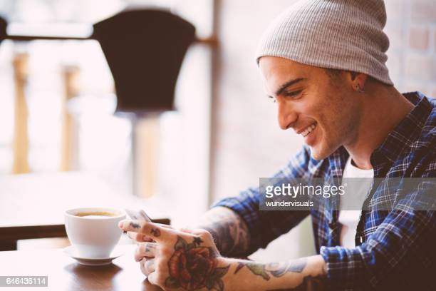 Stylish hipster man sitting at cafe and text messaging