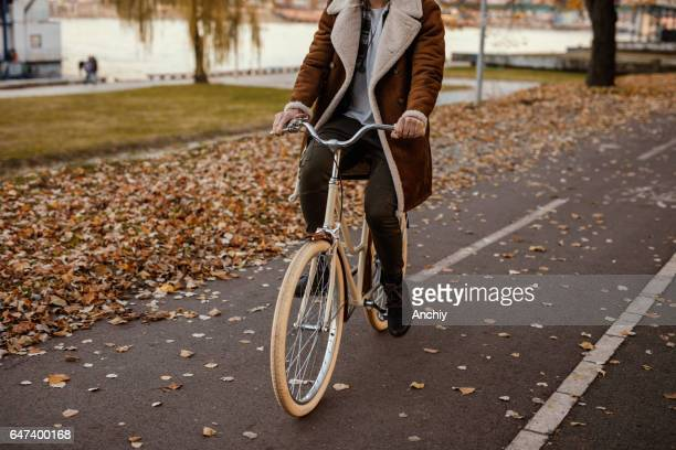 Stylish hipster riding vintage bike in the park in autumn