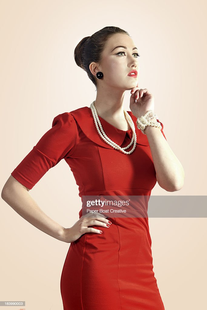 Stylish lady in a red dress looking away