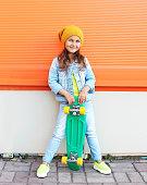 Stylish little girl child with skateboard having fun in city