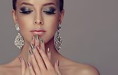 Beautiful woman-model dressed in a big silver earings is showing silver and rose manicure on the nails and rose lipstick on the lips. Fashion makeup and cosmetic.
