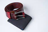 Stylish men accessories. Notebook, brown leather belt and a black wallet on a white background.
