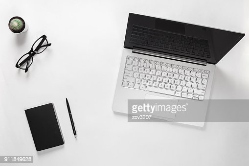 Stylish minimalistic desk table with laptop, cactus, eyeglasses, notebook and pen. Workspace of bloggers, students, freelancers : Stock Photo