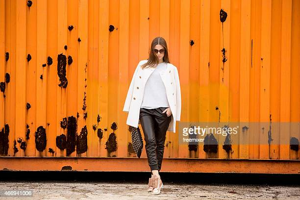 A stylish model posing next to a rusty container