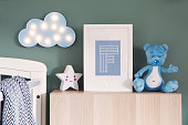 Modern baby interior with green background wall - cute nursery.