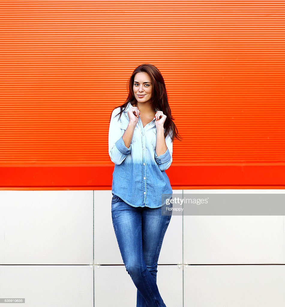 Stylish pretty smiling woman posing against colorful wall in sum : Stock Photo
