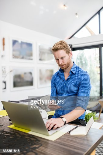 Stylish red haired man typing information that he got from laptop. Worplace, home office. : Stock-Foto