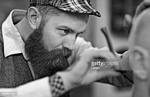 Stylish retro bearded barber with a bald male client