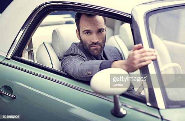 Stylish retro dressed man driving vintage car