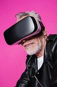 Stylish smiling senior man in leather jacket wearing virtual reality headset