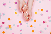Stylish trendy female pink and blue manicure. Beautiful young woman's hands on pink pastel background with festive multicolored confetti.