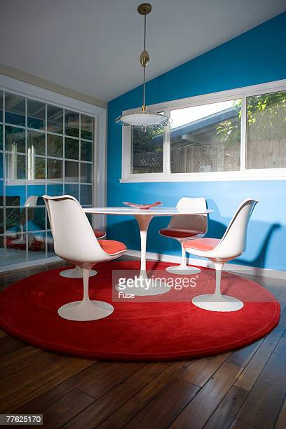 Stylish white chairs and a dining table are placed on a red mat under the lamp