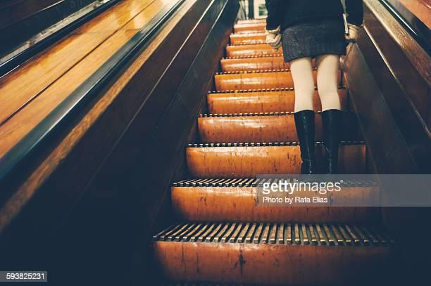 Stylish woman going up escalator