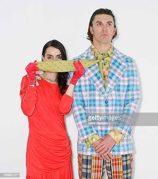 Stylish Woman Hiding Behind Man's Tie