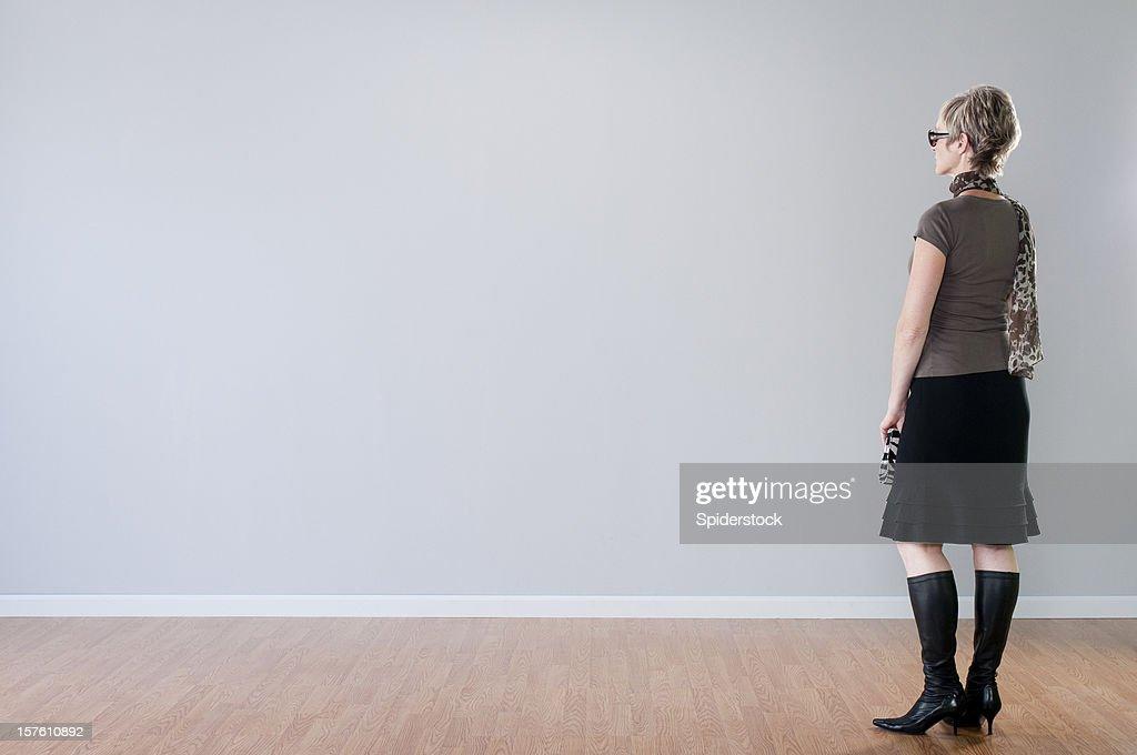 Stylish Woman Looking At Blank Wall : Stock Photo