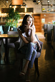 Stylish woman sitting at cafe and wearing white blouse with ethnic jeans. Concept of fashion and beauty.