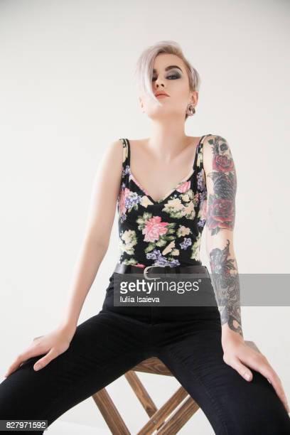 Stylish woman with tattoos posing