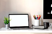 Stylish workspace with laptop, coffee mug and designer or office supplies at home or studio. Mock up.
