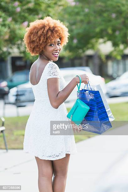 Stylish young black woman with shopping bags