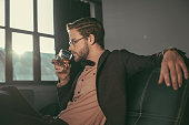 stylish young businessman in eyeglasses and bow tie drinking whiskey