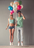 Full length portrait of stylish young couple in sun glasses holding balloons and jumping, on gray background