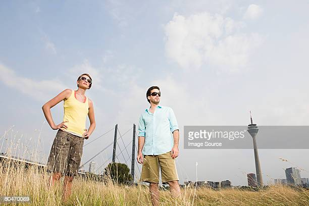 Stylish young couple standing in a field