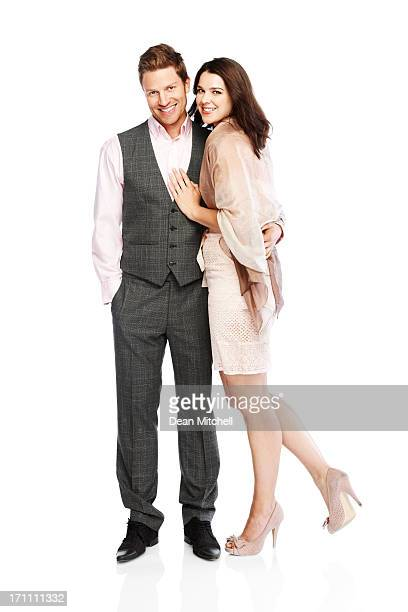 Stylish young couple standing together on white